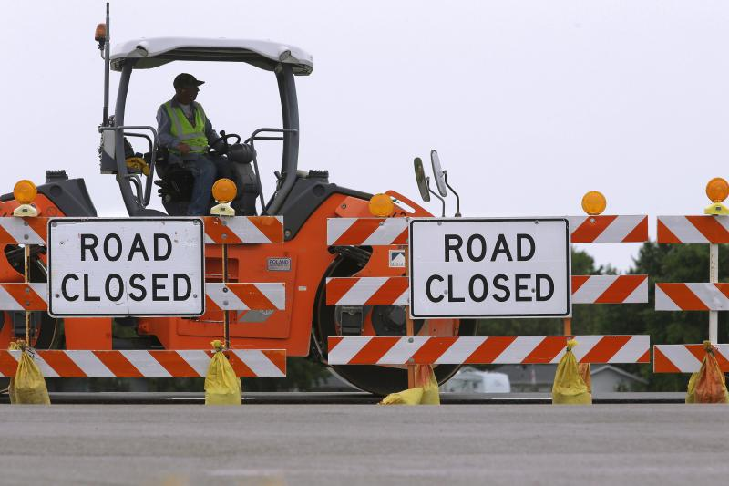 Crews near Road Closed signs