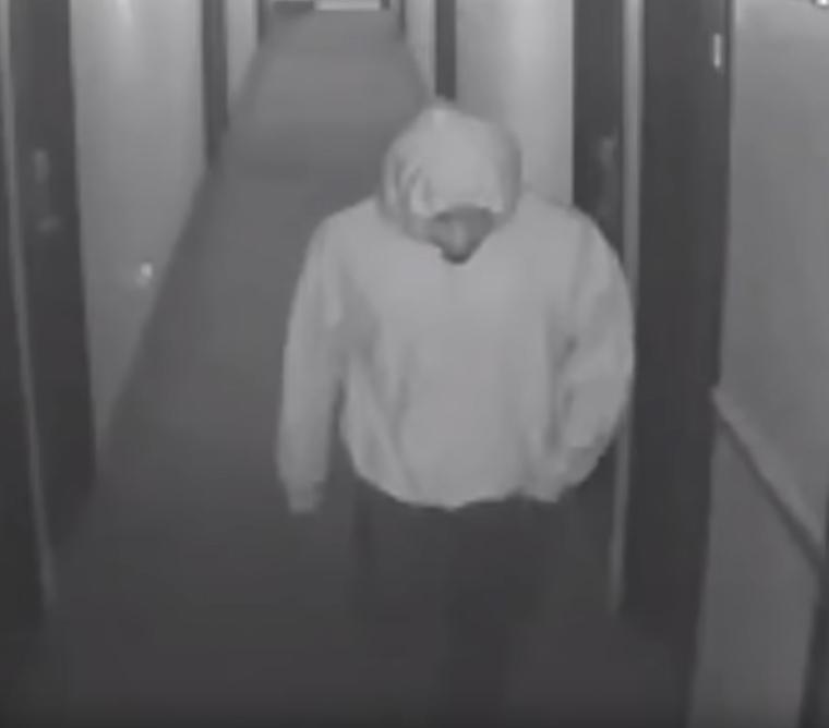 Suspect walks down hallway