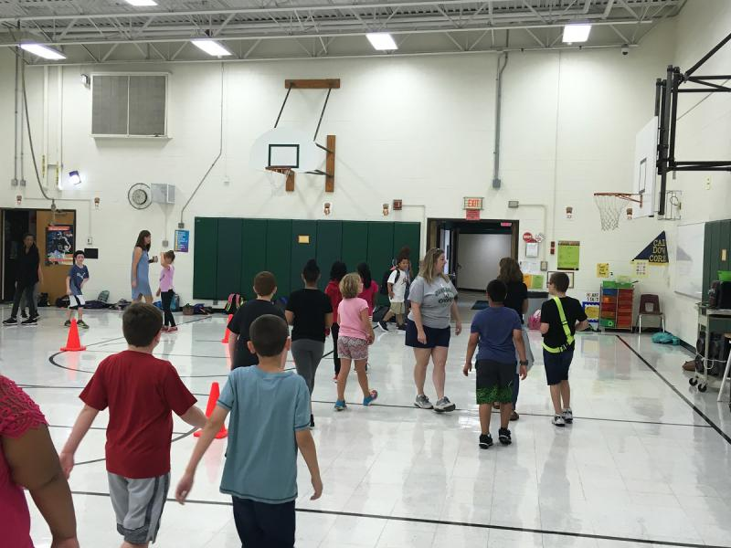 Oakland Elementary students run around the gym