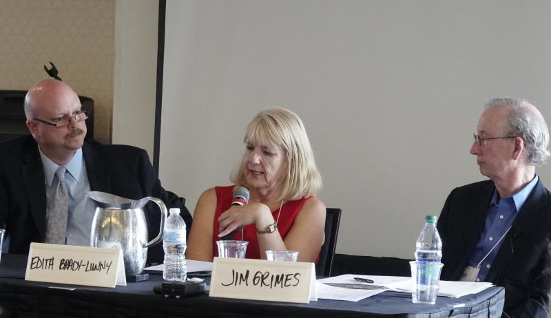 Two men and a woman in the center with a microphone sitting as panelists