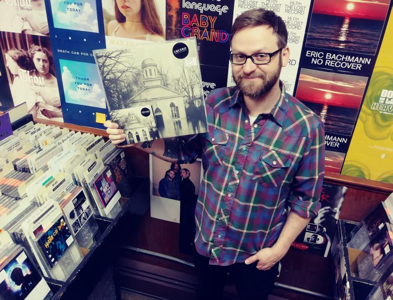 Jared Alcorn holding Lucero's 'Among The Ghosts' LP