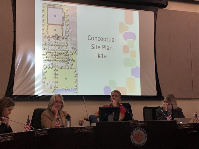 A city council dais and a map of the proposed Bloomington Library expansion.