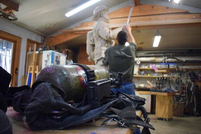 Artist Andrew Jumonville working on his firefighter sculpture inside his backyard shop in Bloomington.