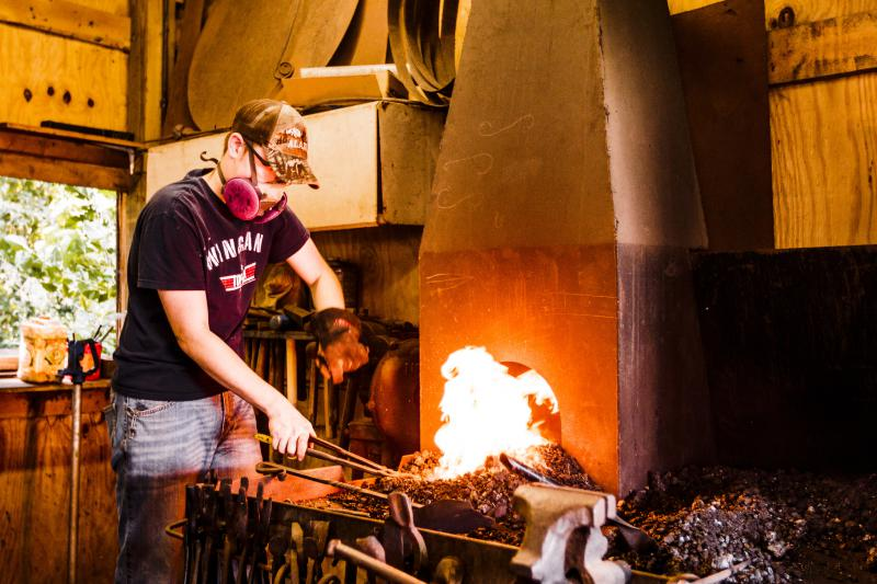 A blacksmith grabs a piece of metal buried deep in the coals of his forge.
