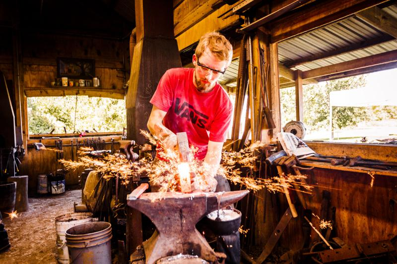 A blacksmith practices his craft, shaping and compressing a red hot block of metal by pounding with his hammer.