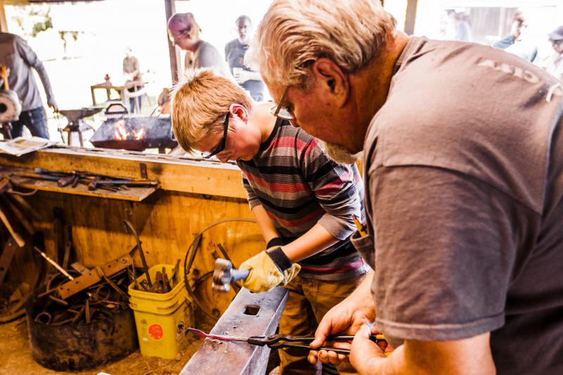 A young blacksmith at work shaping a leaf out of metal.