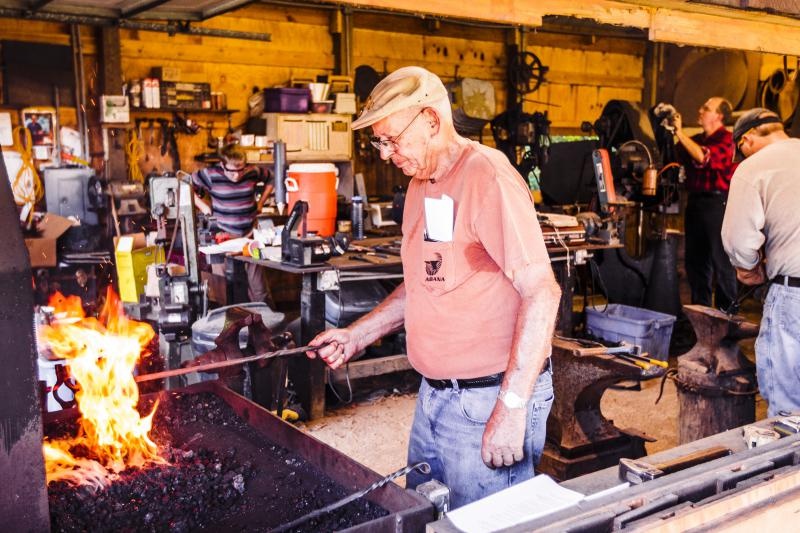 This veteran blacksmith knows his metal rod is long enough not to use tongs.