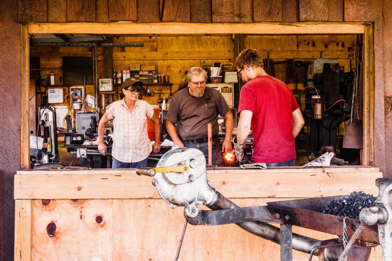 Instructors and students look on to see how the blacksmith shapes his work.