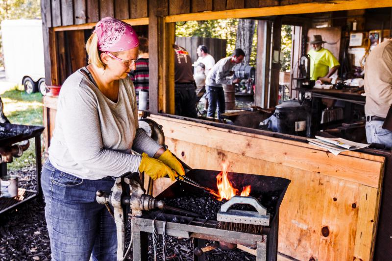 A student of the IVBA's blacksmithing class tends to her forge.