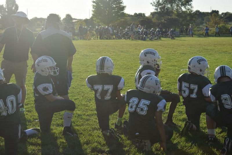 Members of the Bloomington Knockers youth football program kneel on the sidelines as they watch their teammates during a game on Sept. 5.