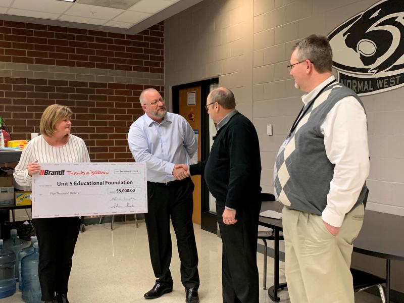 Brandt Industries presents a $5,000 check to the Unit 5 Education Foundation following an early December bus crash that killed two adults and left two others hospitalized.