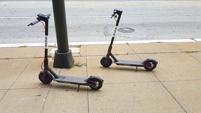 Two electric scooters parked on a sidewalk