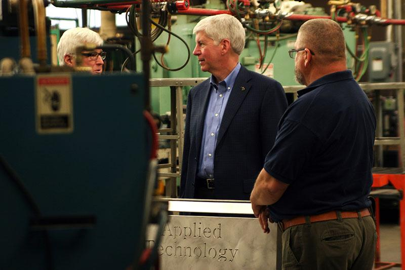 Governor Rick Snyder speaks with Muskegon Community College instructors and staff during a tour of campus skilled trades facilities.
