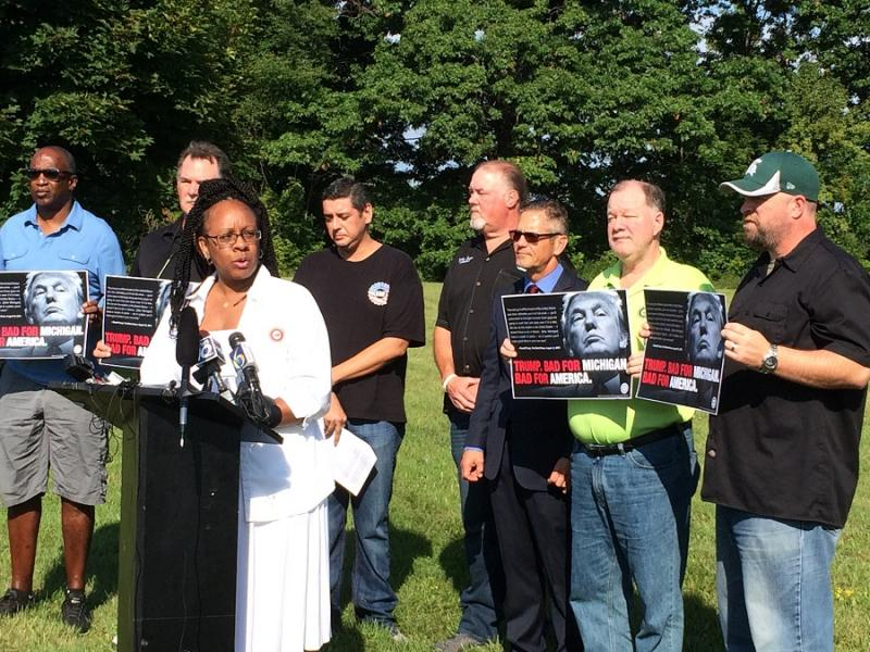 UAW Local 602 autoworker Anita Dawson says Trump's policies are a threat to working families at a demonstration held before a Trump rally on Friday.