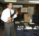 Chief Evangelous exhibits the AK-47 seized in the arrests.