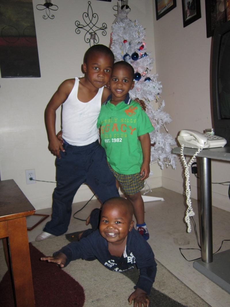 Camron (top left), Juelz (top right), and Ishmel embracing in front of their Christmas tree.