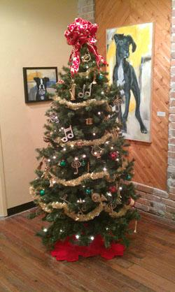 "The tree in WHQR's lobby, with paintings from Clair Hartman's ""Faithful"" series now on display."