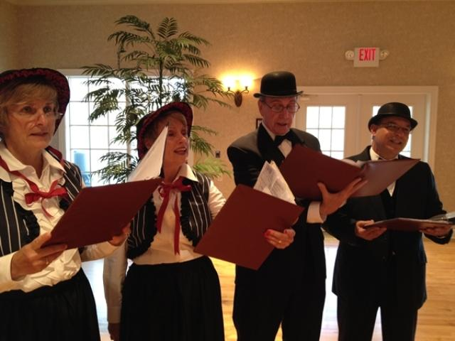The Merry Madrigalers practice for their role as carolers in the first Charles Dickens Christmas Festival. L to R:Susan Desloge, Joanne Masino, Tom McCune and Larry Bochiaro