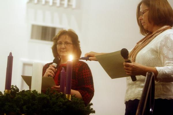 Jamie Cook, left, looks on as Shari Ulman lights the Advent Wreath during Hanging of the Greens Service at United Advent Christian Church in Wilmington, N.C. Sunday December 2, 2012