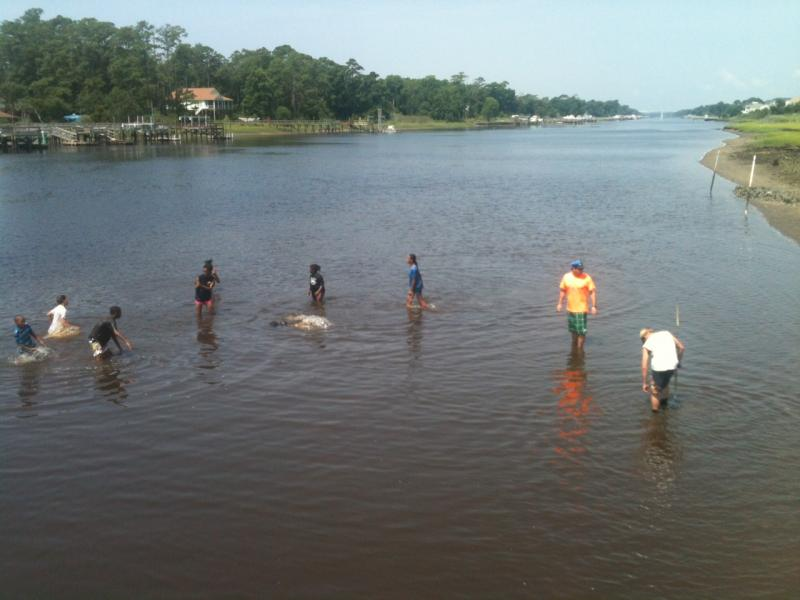 The Boys and Girls Club of Southport takes a splashy break from carefully placing erosion-curbing oyster shells along the banks of the waterway.