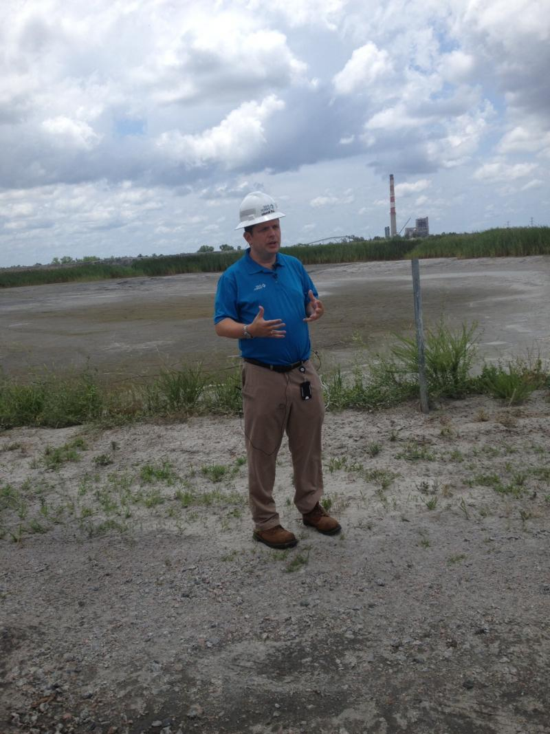 Duke Energy spokesperson Jeff Brooks stands before a dried ash basin on the grounds of the Sutton Plant in Wilmington.