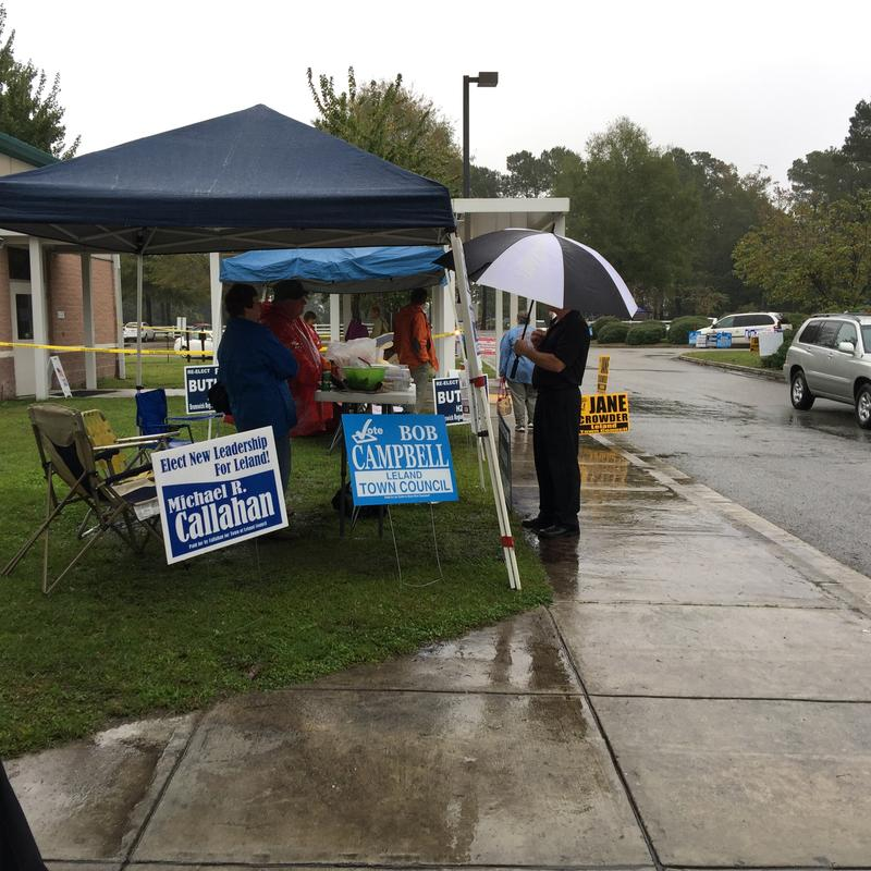 A voter stops to visit with campaign representatives at Belville Elementary School in Brunswick County on Election Day 2015.
