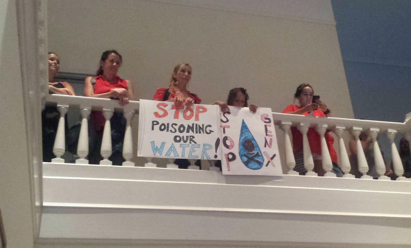 Citizens hold signs protesting GenX and Chemours from the balcony at City Hall.