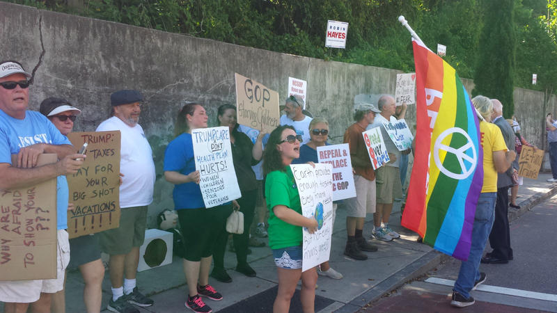 Protesters line the sidewalk opposite the GOP Convention in Wilmington on Saturday.