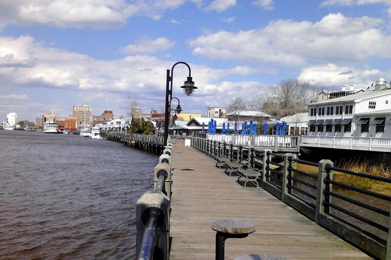 The Wilmington Riverwalk in North Carolina along the Cape Fear River with downtown Wilmington in the background.