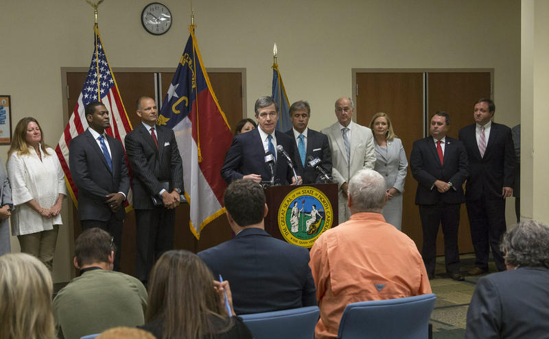Gov. Roy Cooper, center, speaks with the public and the media after Monday's GenX meeting.