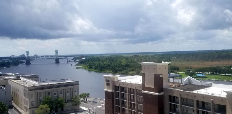 The development would be in the wooded area to the right and upriver from the Cape Fear Memorial Bridge.