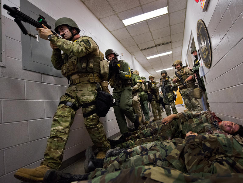 Members of the Crestview Police Department SWAT team move past the bodies of simulated victims to clear the Naval School Explosive Ordnance Disposal building during an active shooter exercise on Eglin Air Force Base, FL.