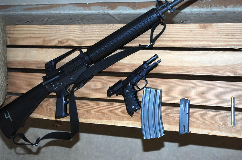 A rifle and handgun lay next to their magazines at the base shooting range.