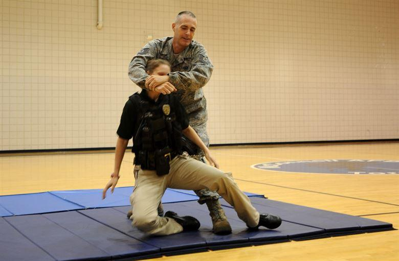 "Rebecca Johnson, Wichita Police Department patrol officer and department defensive tactics instructor, demonstrates the self-defense maneuver, the ""limp noodle,"" during a women's self defense class June 27, 2013, at McConnell Air Force Base."