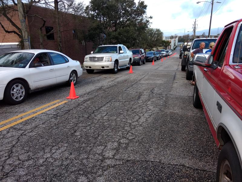 A long line of cars waited for an emergency food distribution to begin Tuesday near the downtown campus of Cape Fear Community College.