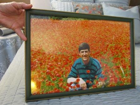 Ann Deveny holds a photo of her husband Dan, an impromptu shot in a German poppy field. Dan now suffers from early-onset Alzheimer's.