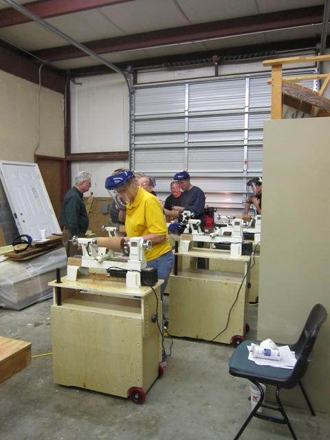 Students of Byron Rosbrugh's woodturning class gather around their lathes in the shop at Cape Fear Community College. .