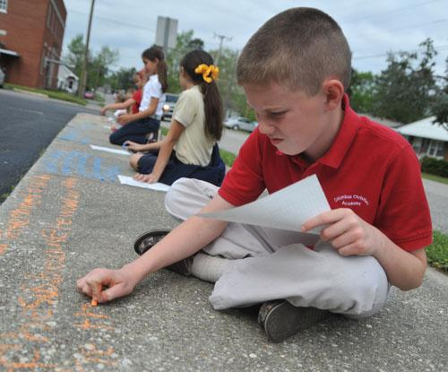 Students from Columbus Christian Academy write parts of The New Testament on Whiteville's sidewalks April 3 as a test run of the Walk with Jesus New Testament Writing set for Easter Sunday 2012.