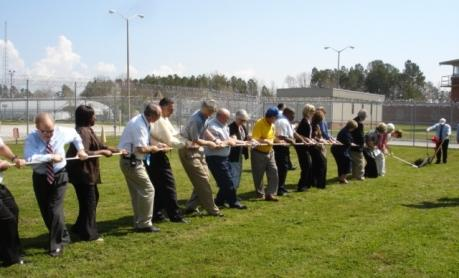 Attendees at Pender Correctional Institution pull a plow to break ground on a new chapel there.