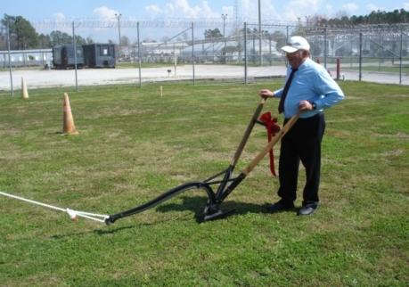 Chaplain Jimmy Joseph at the helm of the plow breaking ground for the new prison chapel.