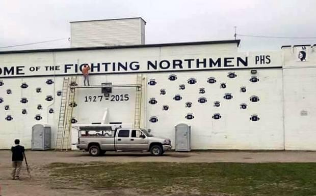 """A painter replaces the word """"fighting"""" on the bleachers at Curtis Field in Petoskey."""