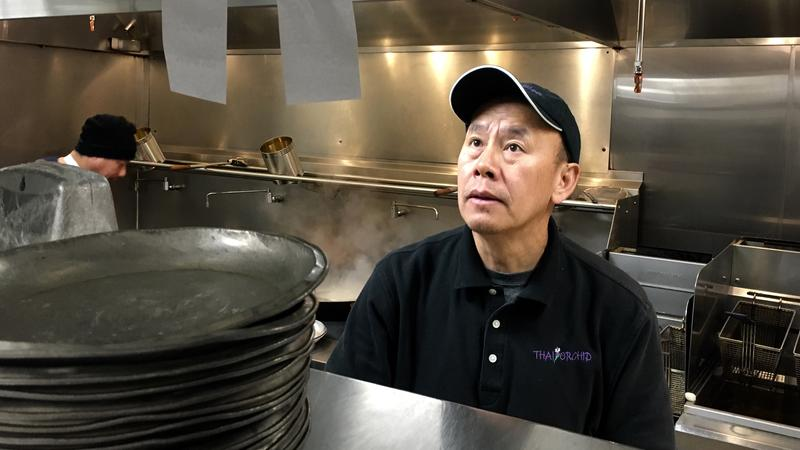 Thongsai Vangyi checks an order slip while cooking in his restaurant, Thai Orchid, in Petoskey.