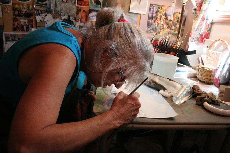 Peggy McNew gets up close and personal with her watercolor painting. She has cone dystrophy, and uses her lower peripheral vision to see.