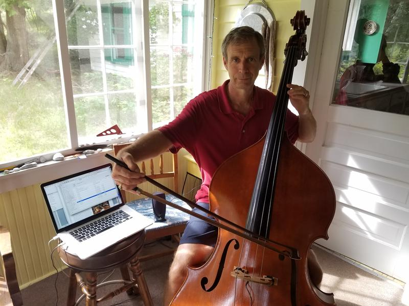 Paul Erhard performs on his double bass, in the back porch of his home in Pierport, Michigan.