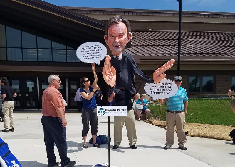 The group Oil and Water Don't Mix hold up a puppet of Michigan Attorney General Bill Schuette outside the meeting.