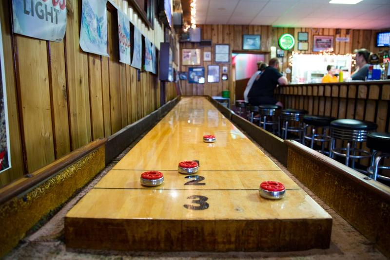 A shuffleboard table inside the No Place Special Log Bar & Grill.