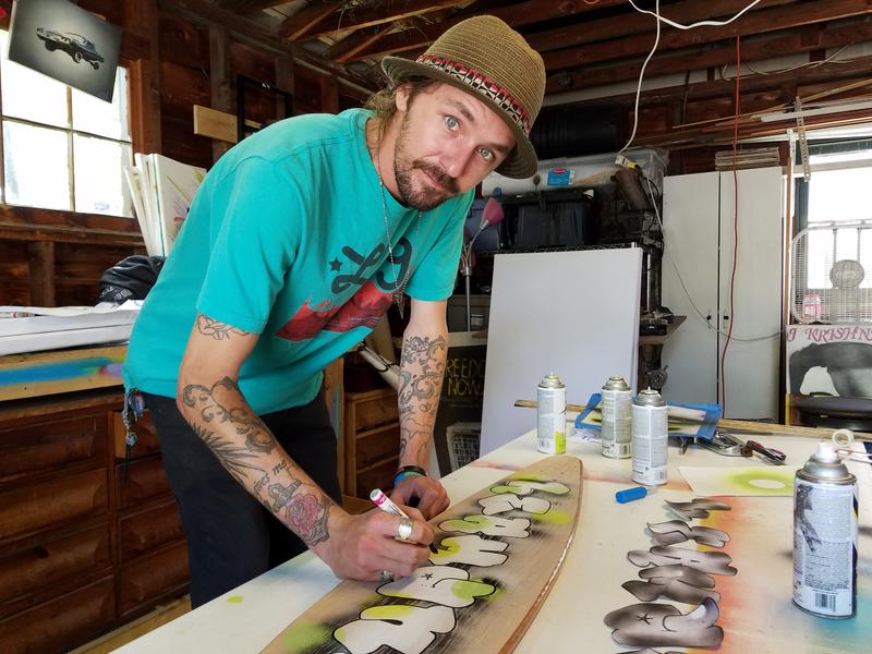 Chase Hunt paints on a longboard in his garage in Traverse City.