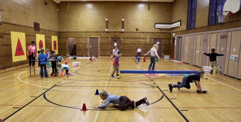 Students spin, balance, jump and walk at different stations in the gym at Central Grade School in Traverse City. Each movement is designed to help train the brain to read better.