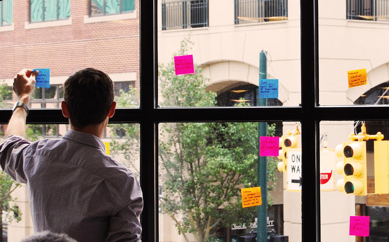 20 Fathoms Executive Director Andy Cole places sticky notes on a window overlooking Front Street in Traverse City.