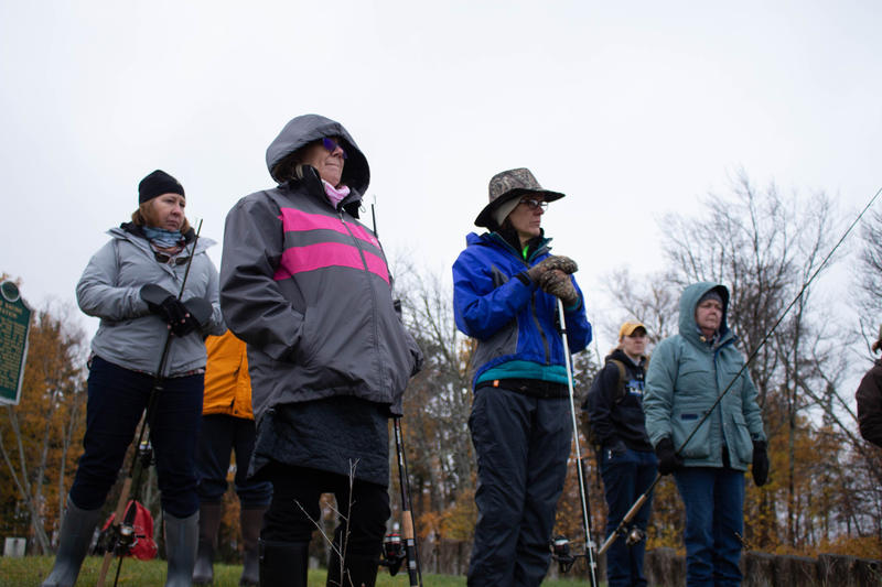 Female anglers stand along the Two Hearted River, watching as a class instructor demonstrates casting.